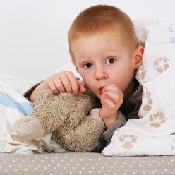 Petit garçon avec son doudou dans son lit