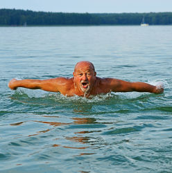 Senior qui nage dans un lac