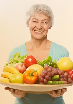 Femme de 60 ans qui porte des fruits et légumes