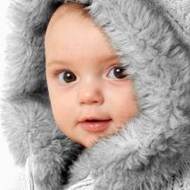 bébé emmitouflé dans un manteau de fourrure hivernal