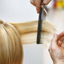 Coiffeur qui peigne les cheveux d'une cliente