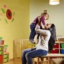 Professionnelle de la petite enfance avec une petite fille en crèche